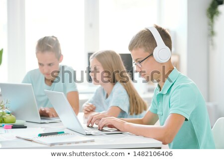 one of youthful classmates in headphones looking at laptop display stock photo © pressmaster
