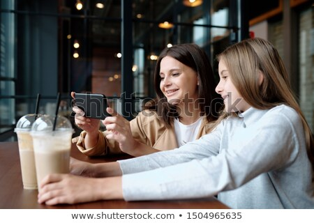young smiling woman and her cute daughter watching curious video in smartphone stock photo © pressmaster