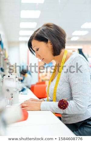 Alterations tailor in her studio working in some clothes Stock photo © Kzenon