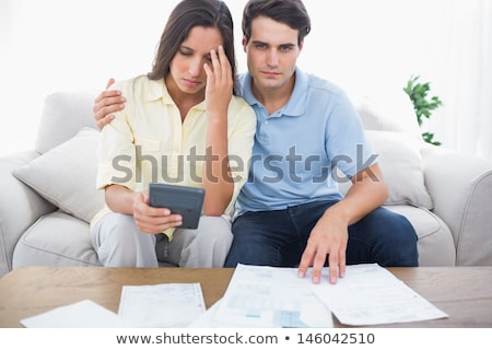 Fearful couple doing their accounts sat on a couch Stock photo © Lopolo