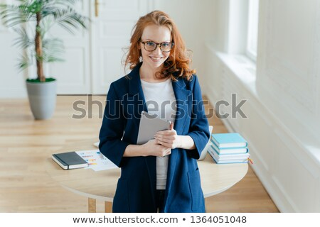 Happy good looking female office worker enjoys online banking service, checks balance on touch pad,  Stock photo © vkstudio