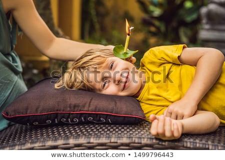 The boy gets a procedure with an ear candle, children's ears health, good hearing, earwax Stock photo © galitskaya