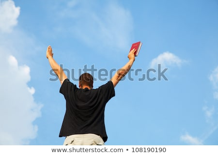 Young man staying with raised hands against blue sky Stock photo © AndreyKr