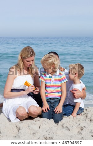Attentive mother at the beach with her daughter in the sun Stock photo © wavebreak_media