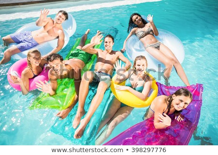 attractive blond girl lying in swimming pool stock photo © pawelsierakowski
