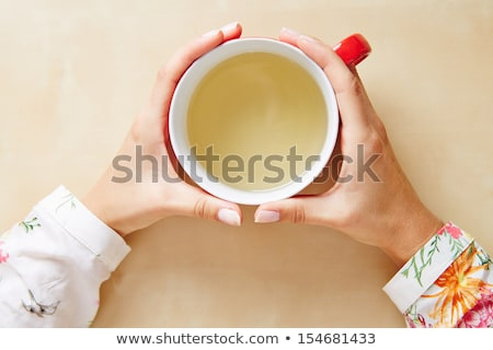 Woman holding a teacup in two hands Stock photo © sarahdoow