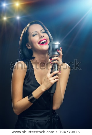 portrait of a beautiful brunette with a retro microphone stock photo © nejron