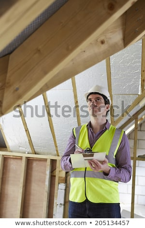 Foto d'archivio: Building Inspector Looking At Roof Of New Property