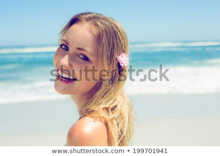 fit woman in bikini standing on the beach smiling at camera stock photo © wavebreak_media