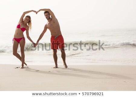 Montare donna sorridente bikini spiaggia a forma di cuore Foto d'archivio © wavebreak_media