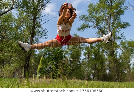 Attractive woman doing acrobatic stunt Stock photo © deandrobot