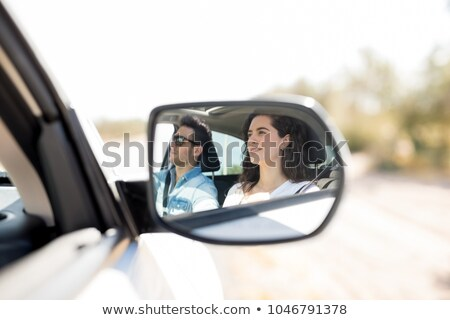 Stock fotó: Young Man Driving A Car Reflected In The Wing Mirror