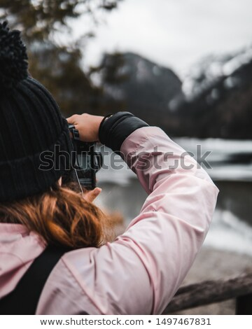 concenrated woman photographer standing and taking pictures in mountains stock photo © deandrobot