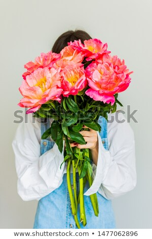 pretty young woman covered her face with bouquet of flowers stock photo © deandrobot