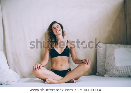 Happy relaxed young woman in swimwear sitting with legs crossed Stock photo © deandrobot