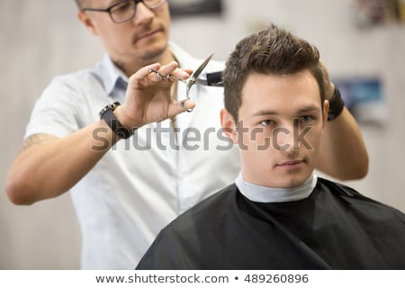 Handsome man getting haircut by hairdresser Stock photo © deandrobot