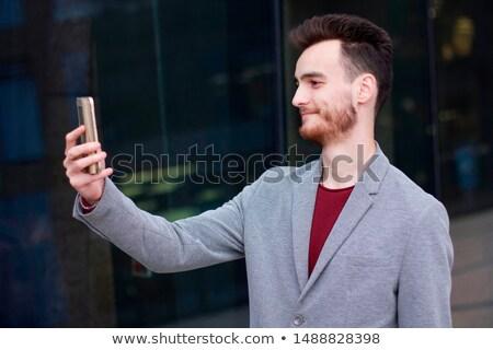 junger · Mann · sprechen · mobile · lächelnd · Sitzung · Sofa - stock foto © deandrobot