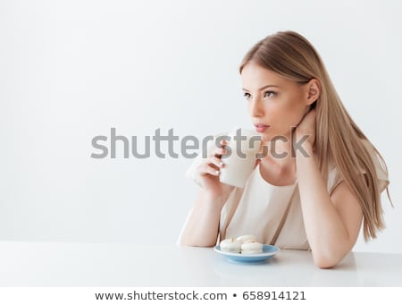 Young lady sitting isolated near sweeties drinking coffee Stock photo © deandrobot