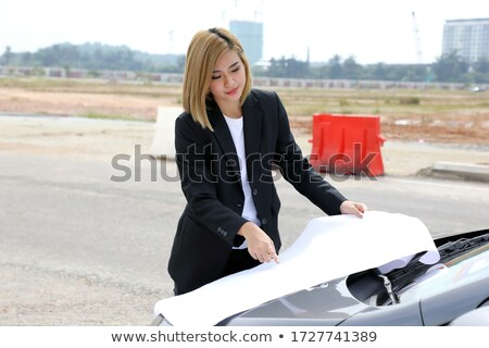 Woman pointing from car at building site Stock photo © IS2