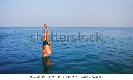 Man climbing out of swimming pool Stock photo © IS2
