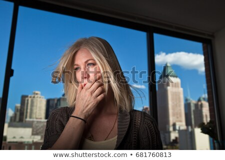 Mature woman looking anxious in office with cityscape visible behind Stock photo © IS2
