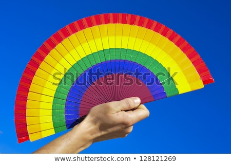 man with a rainbow-patterned hand fan Stock photo © nito
