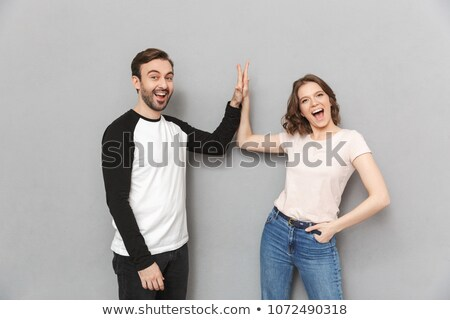 Emotional couple friends gives a high five to each other. Stock photo © deandrobot