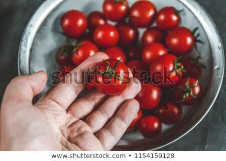 hand selects and shows whole fresh cherry tomatoes in a colander Stock photo © TanaCh