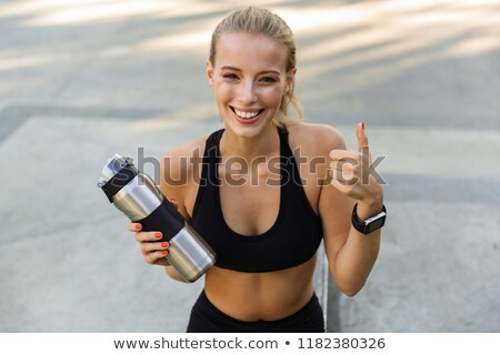 blonde sports woman in park holding bottle with water showing thumbs up gesture stock photo © deandrobot