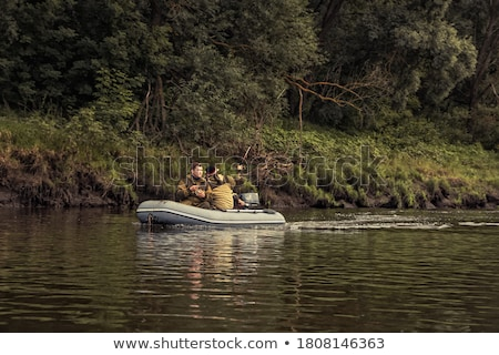 fisherman fishing from motorboat and from bank stock photo © robuart