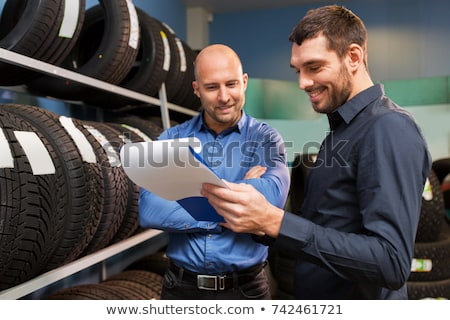 auto business owner and wheel tires at car service Stock photo © dolgachov