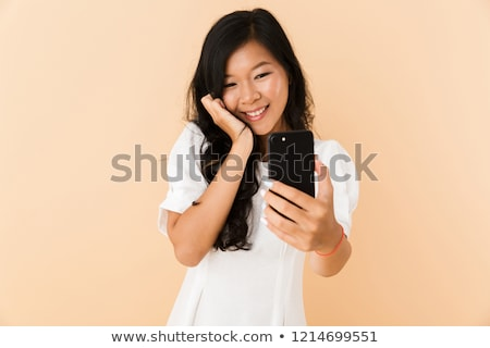 Happy asian woman posing isolated over beige wall background talking by phone. Stock photo © deandrobot