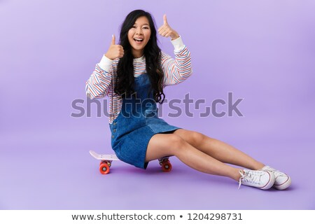 Asian beautiful attractive woman posing isolated indoors sitting on skateboard. Stock photo © deandrobot