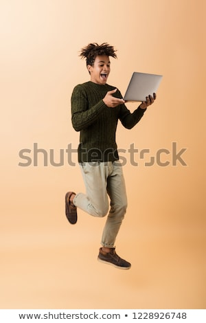 Full length photo of joyous african american guy wearing sweater Stock photo © deandrobot