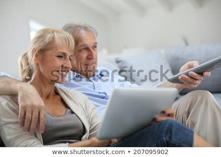 senior woman with remote watching tv at home Stock photo © dolgachov