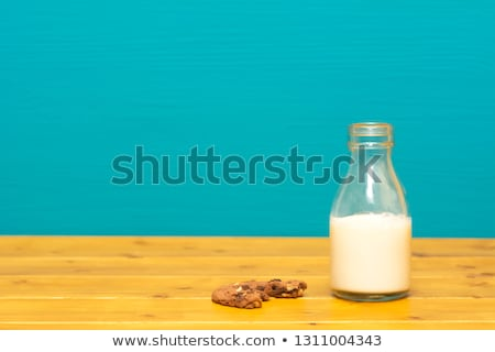 half full milk bottle and a half eaten chocolate cookie stock photo © sarahdoow