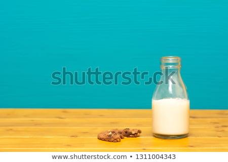 Half full milk bottle and a half-eaten chocolate cookie Stock photo © sarahdoow