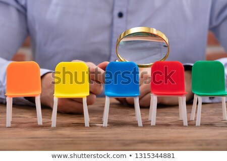 businessperson looking at vacant chairs through magnifying glass stock photo © andreypopov