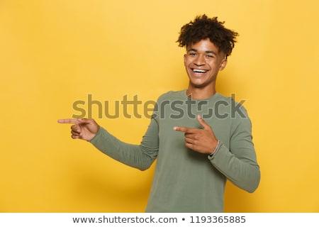 Portrait of pleased african man having stylish afro hairdo point Stock photo © deandrobot
