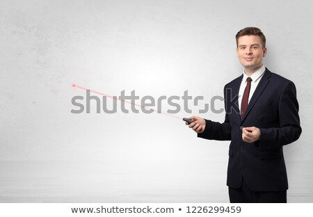 Businessman with laser pointer and copyspace white wall Stock photo © ra2studio
