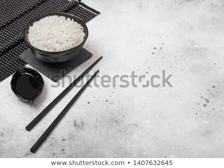 Black bowl with boiled organic basmati jasmine rice with black chopsticks on bamboo placemat on ligh Stock photo © DenisMArt