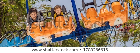Father and son having a ride in the bumper car at the amusement park BANNER, long format Stock photo © galitskaya