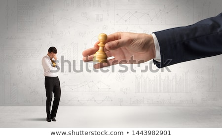 Businessman is afraid to make the next step in a chess game with graphs background Stock photo © ra2studio