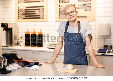 Happy and friendly young barista in apron and t-shirt standing by counter Stock photo © pressmaster
