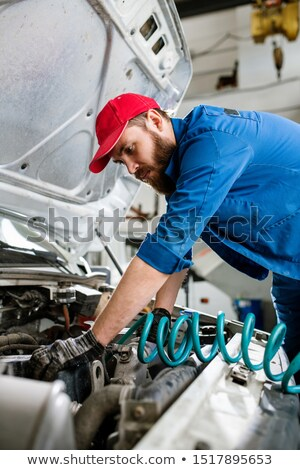 Serious young bearded engineer of maintenance service bending over engine Stock photo © pressmaster