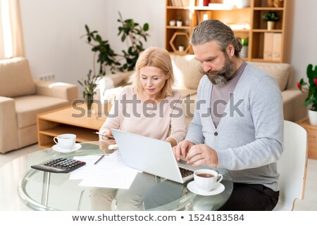 Mature businessman concentrating on network while his colleague reading document Stock photo © pressmaster
