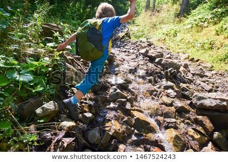 Boy from preschool jumping from stone Stock photo © galitskaya