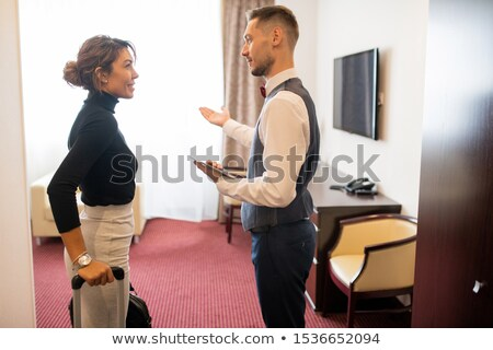 Young porter in uniform showing room to one of guests with baggage Stock photo © pressmaster