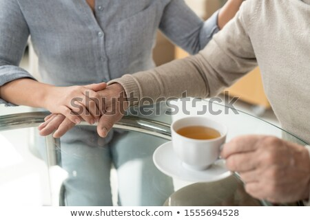 Careful young daughter holding hand of her retired aged father having cup of tea Stock photo © pressmaster
