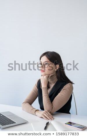 Stock photo: Young serious female economist concentrating on analysis of financial situation